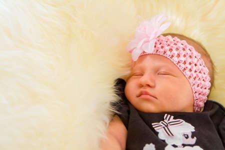 0 1 months: Newborn girl sleeping on fluffy carpet