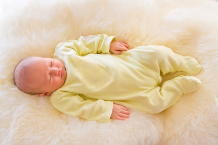 Newborn girl sleeping on fluffy carpet photo