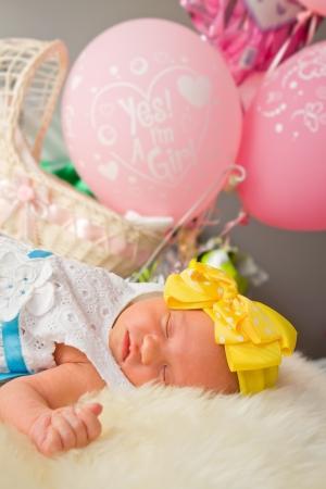 0 1 months: Newborn girl sleeping by pink balloons
