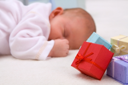 Colorful gift boxes with sleeping baby in background