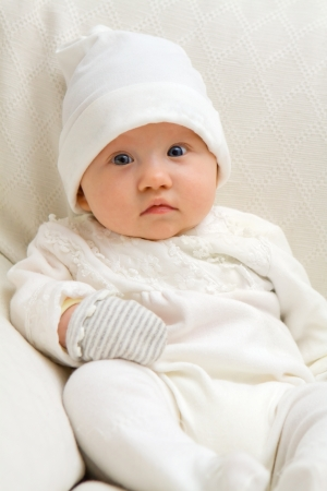 Sweet baby sitting on couch wearing white Stock Photo - 17966992