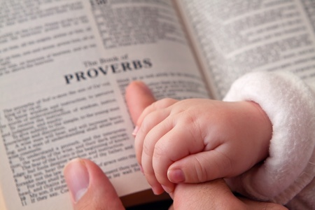 the sermon: Baby holding father s finger as he points to Proverbs verse  Stock Photo