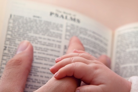 the sermon: Baby holding father s finger as he points to Psalms verse
