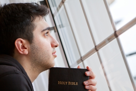 Young man looking outside with Bible in hand