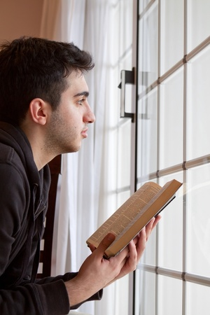 Young man looking outside with open Bible in hand