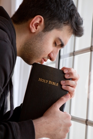 hombre orando: Hombre joven que sostiene la Biblia y orando por la ventana
