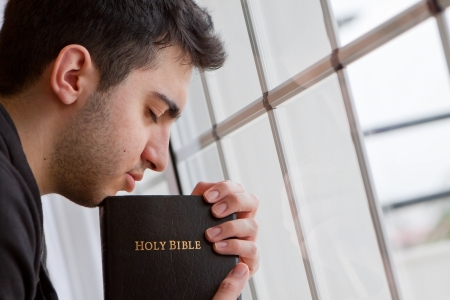 Young man holding Bible and praying by window Stock Photo - 18600530