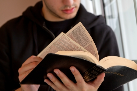 christian faith: Young man reading the Bible