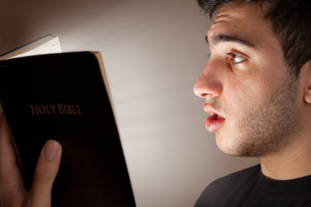 realiseren: Jonge man verbaasd en geïntrigeerd door open Bijbel