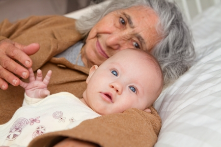 Great Grandma and great granddaughter snuggling on white sheet Stock Photo - 19225210
