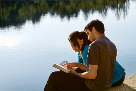 Two young adults sitting by a lake and studying the Bible (King James Version) photo