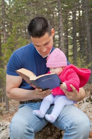 Baby girl sitting on dad's lap reading KJV Bible (King James Version)
