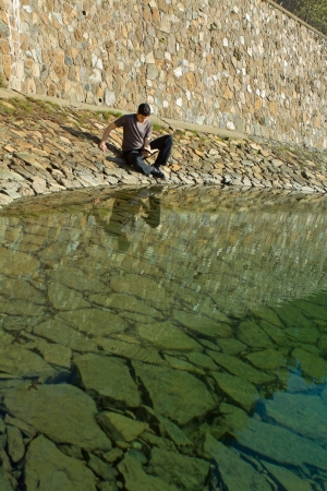 Young man sitting by a lake reading the Bible  photo