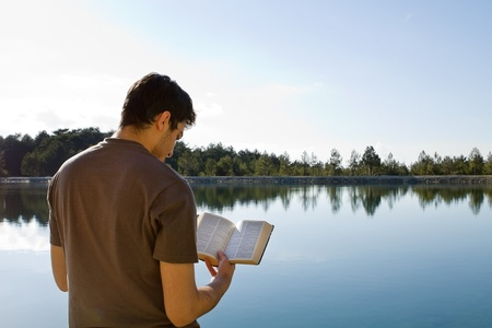 Young man in front of lake reading the Bible