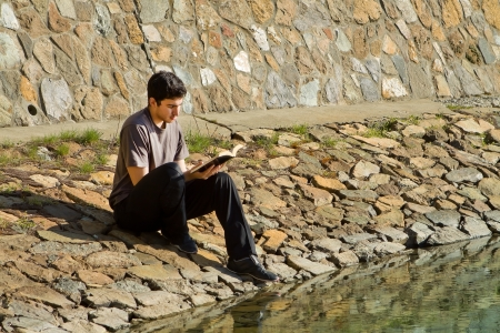 Young man sitting by a lake reading the Bible