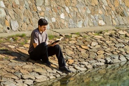 Young man sitting by a lake reading the Bible Reklamní fotografie