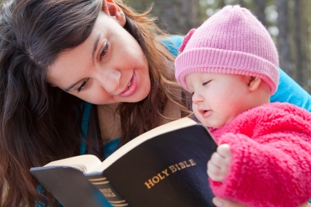 Baby girl and mom reading Bible  Stock Photo