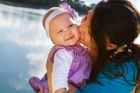 Cute smiling baby receiving a kiss from her mom by a lake Stock Photo