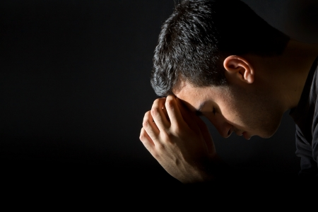 Young man praying in the dark Stock Photo