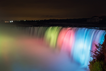 Long exposure of the rushing Niagara Falls lit up at night in different colors