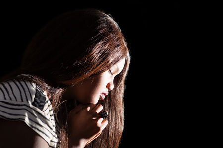 praying: Low key image of young girl praying   Stock Photo