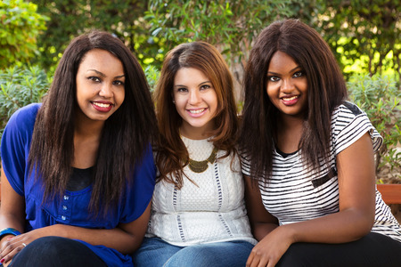 multi ethnic: Three beautiful girls sitting in nature smiling Stock Photo