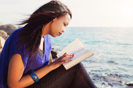 biblia: Hermosa chica leyendo su Biblia junto al mar Foto de archivo