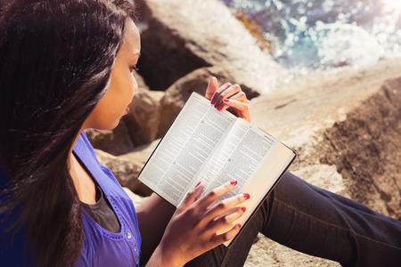 mujer leyendo libro: Chica joven que lee su Biblia junto al mar