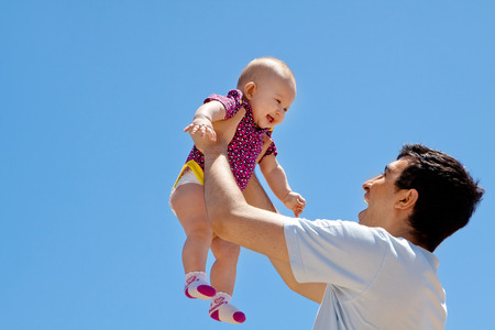 A young father playing with his precious little girl outdoors photo