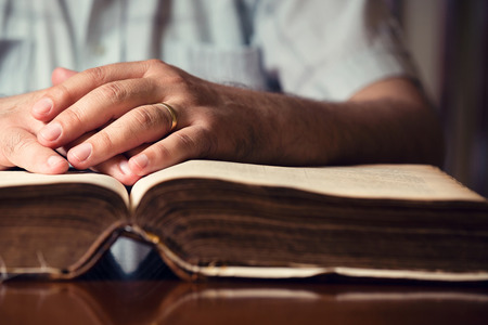 Male hands on 150 year old Bible photo