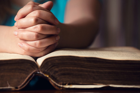 principles: Girl praying with hands on 150 year old Bible