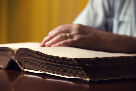 Male hands on 150 year old Bible Stock Photo