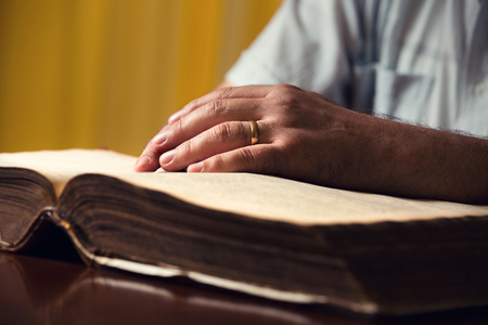 verse: Male hands on 150 year old Bible Stock Photo