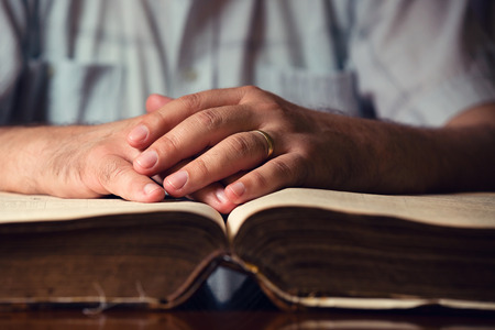 Male hands on 150 year old open Bible Stock Photo