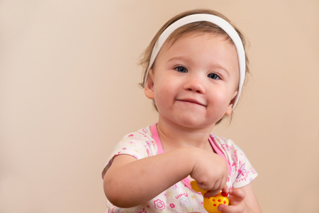 Baby Girl Smiling Holding Toy Looking at Camera
