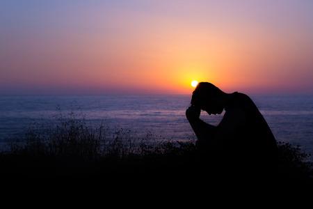 Jonge man, die bidt tot God tijdens zonsondergang aan zee Stockfoto