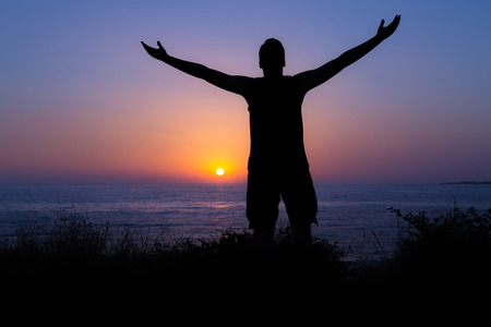 believe: Young man praising and worshiping God during sunset by the sea