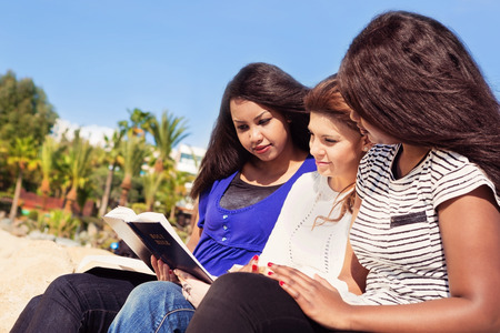 Three young girls reading together on the beach photo