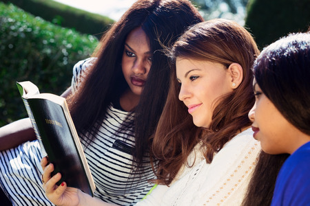 Three Christian girls studying the Bible as a group Stock Photo