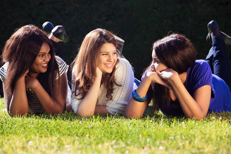 Three girls relaxing and talking outdoors
