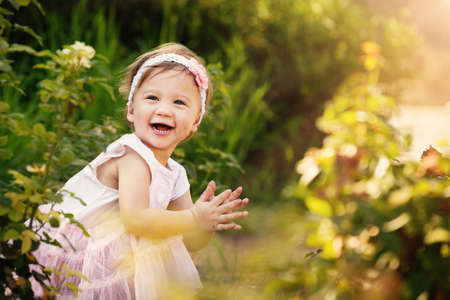 Gorgeous little girl outdoors in green garden having lots of fun photo