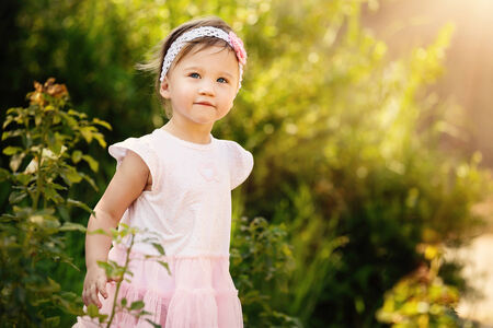 Gorgeous little girl outdoors in green garden