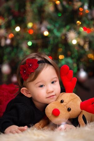 Little Girl Under the Christmas Tree Snuggling with her Reindeer Stock Photo