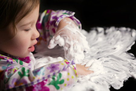 inventive: Little girl enjoying playing with foamy cream Stock Photo