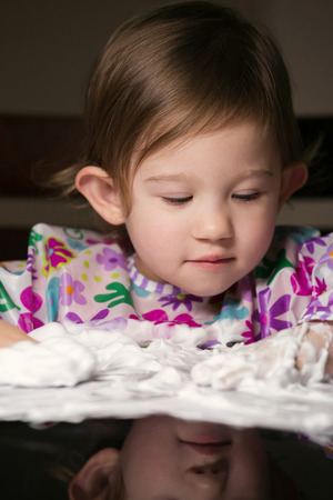 tot: Little girl enjoying playing with foamy cream Stock Photo