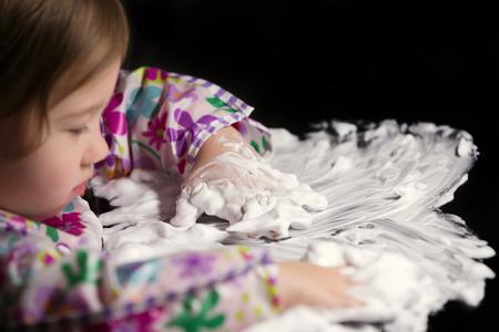 Little girl enjoying playing with foamy cream Stock Photo