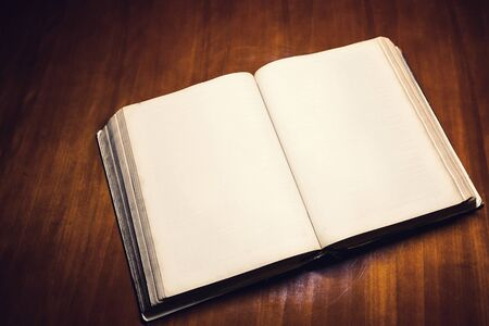 Open old Bible on a wooden background