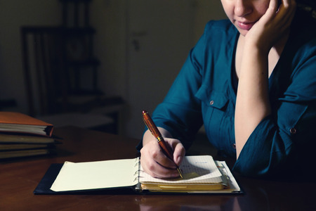 Young lady writing in her notepad late at night