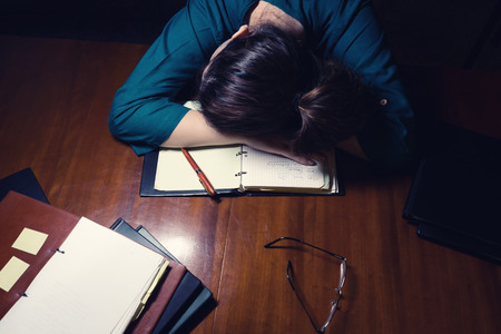 Tired young lady sleeping on her books