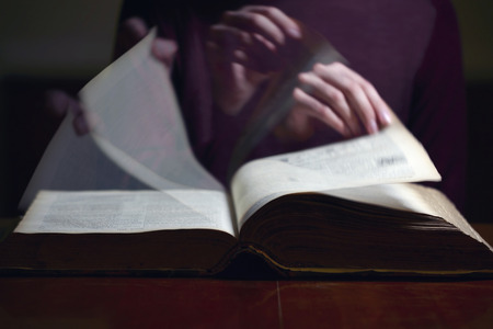 Turning pages of an old book on a desk Stock Photo